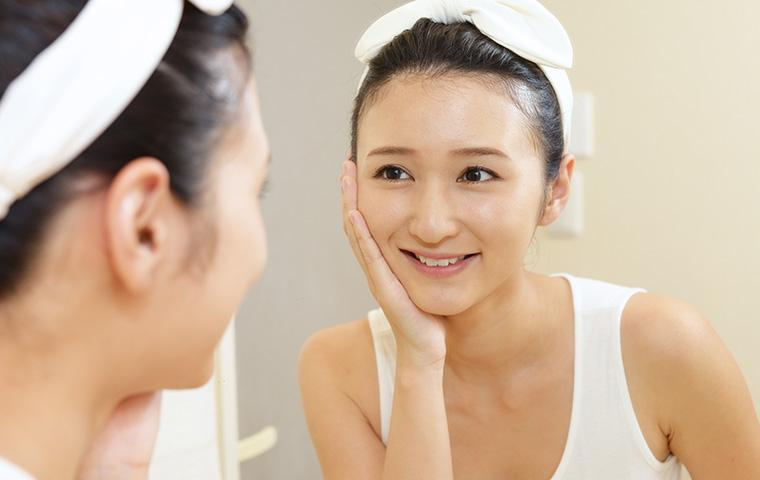 鏡を見て微笑む女性