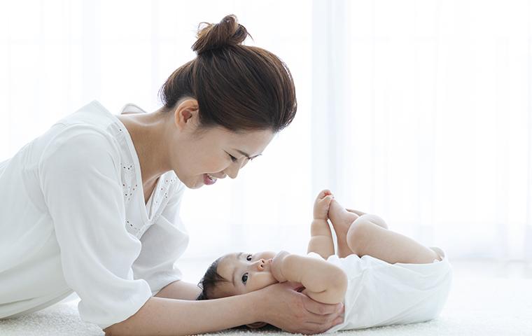 赤ん坊に微笑む女性