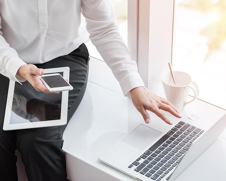 スマホとパソコンとタブレット端末を扱う男性