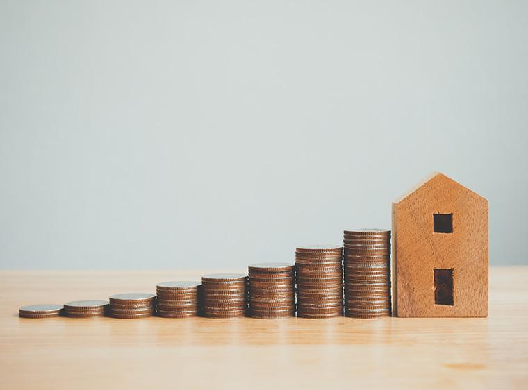 積まれたお金と木の家