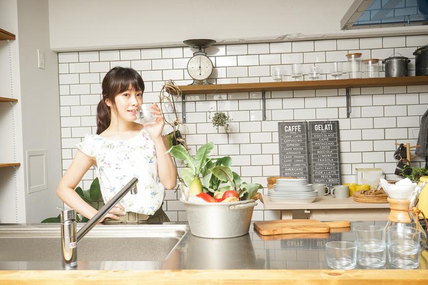 台所で水を飲む女性