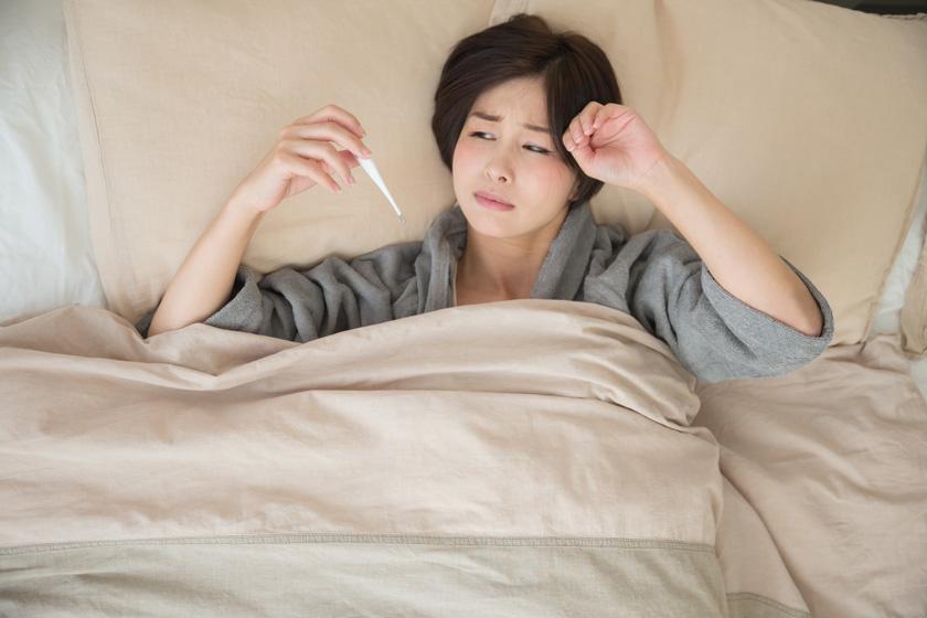 ベッドで体温を測り顔をしかめる女性