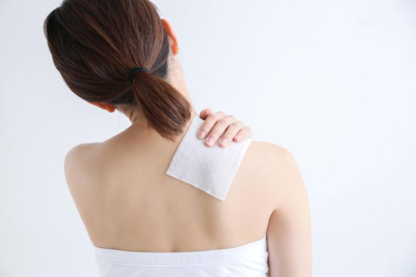 肩に湿布を貼る女性