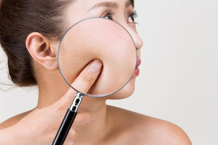虫眼鏡で拡大される女性の肌