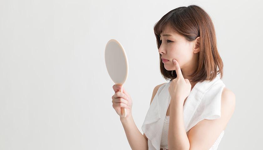 手鏡を見る困り顔の女性