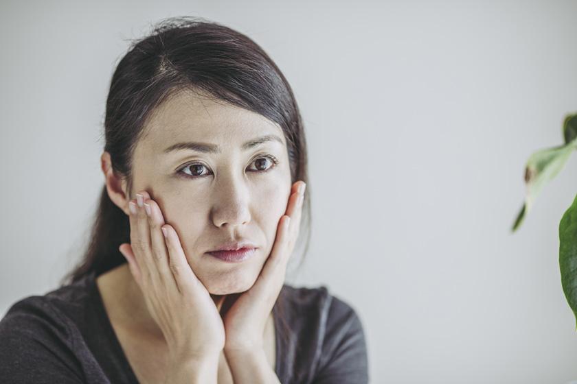 憂鬱そうに自分の肌に触れる女性