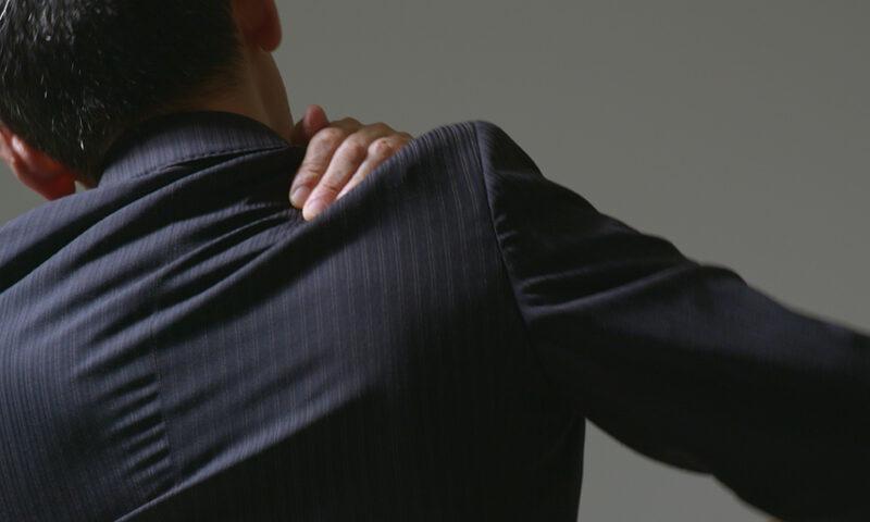 肩凝りのスーツの男性